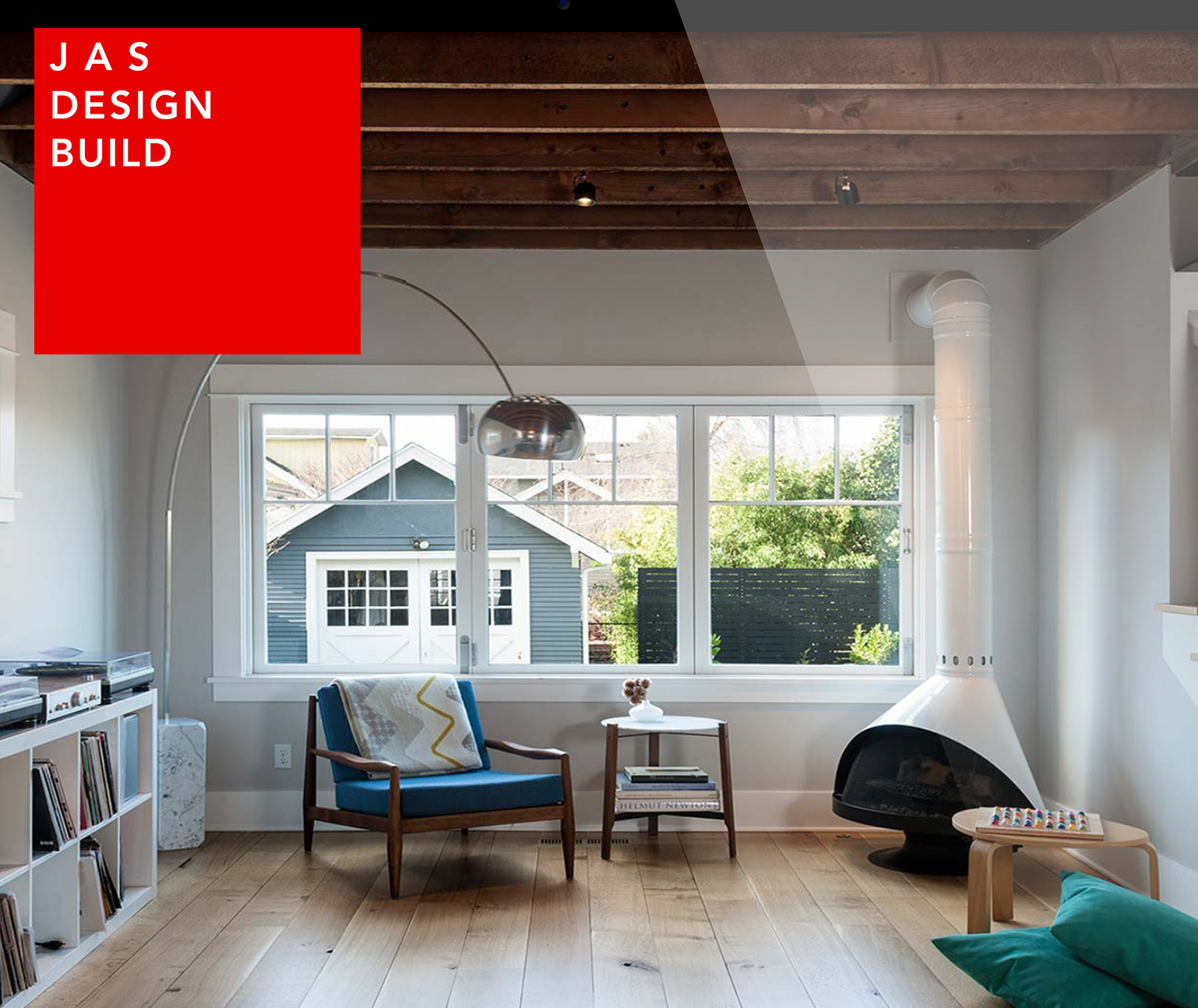 Interior of a modern living room with wood floors, JAS Design Build logo
