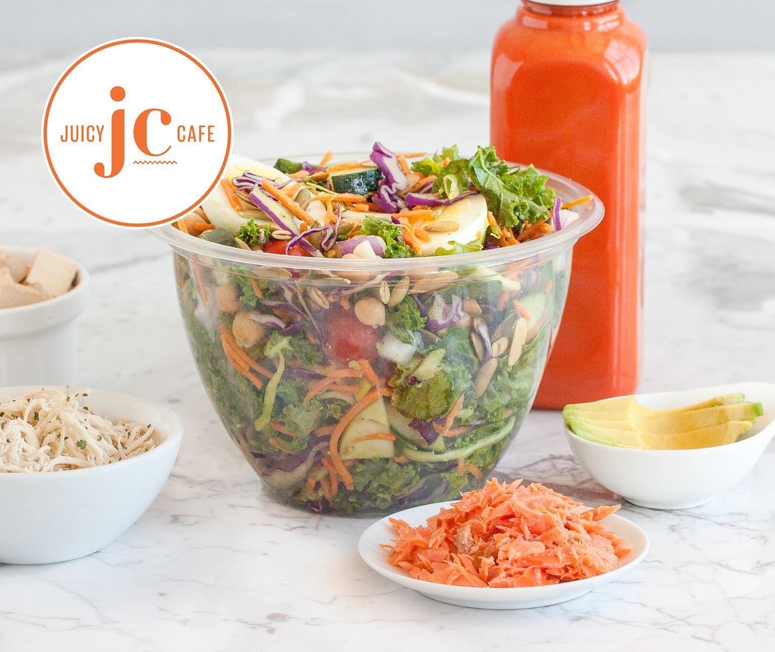 Colorful salad in a plastic bowl with juice in plastic bottle on a marble countertop